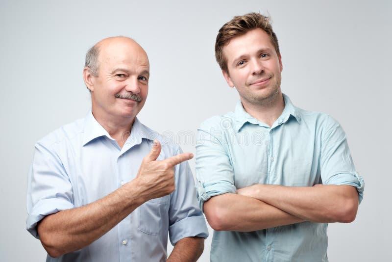 Il padre senior è fiero di suo figlio maturo immagine stock