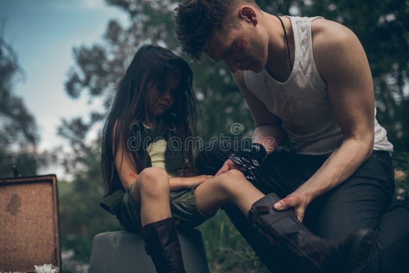 Il padre senza tetto ispeziona la ferita sulla gamba di sua figlia immagine stock libera da diritti