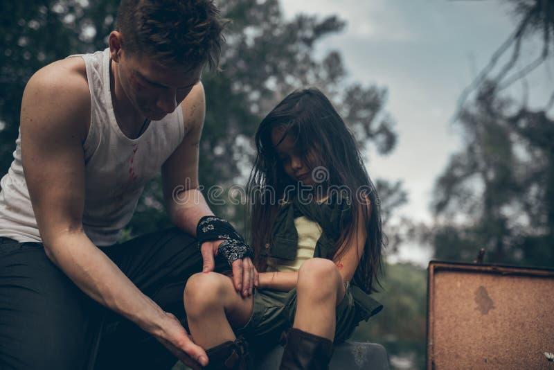Il padre senza tetto ispeziona la ferita sulla gamba di sua figlia immagini stock libere da diritti