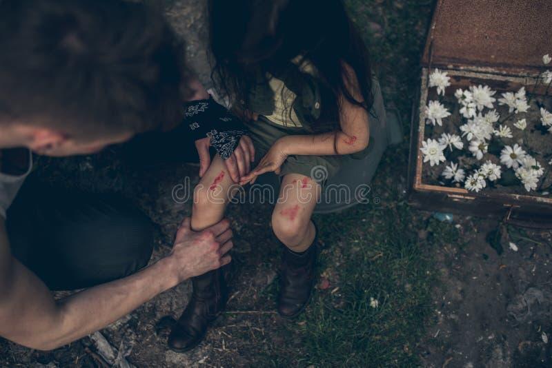 Il padre senza tetto ispeziona la ferita sulla gamba di sua figlia fotografia stock