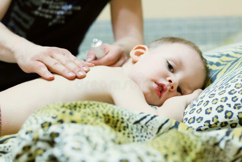 Il padre sfrega la parte posteriore di un bambino malato immagini stock