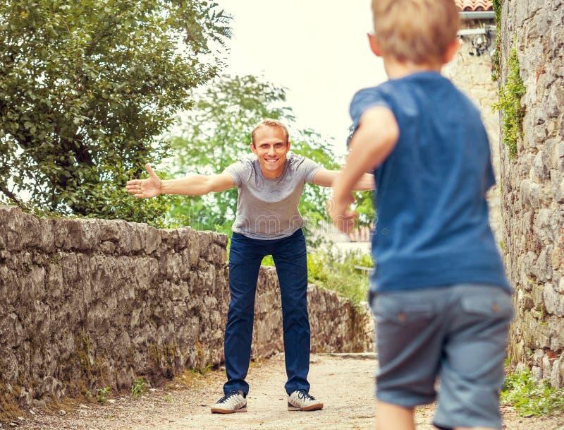Il padre sparge le sue armi per abbracciare il figlio d'avvicinamento fotografie stock libere da diritti