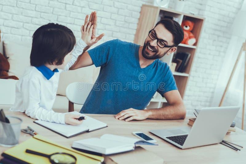 Il padre sta facendo un compito con il figlio immagini stock