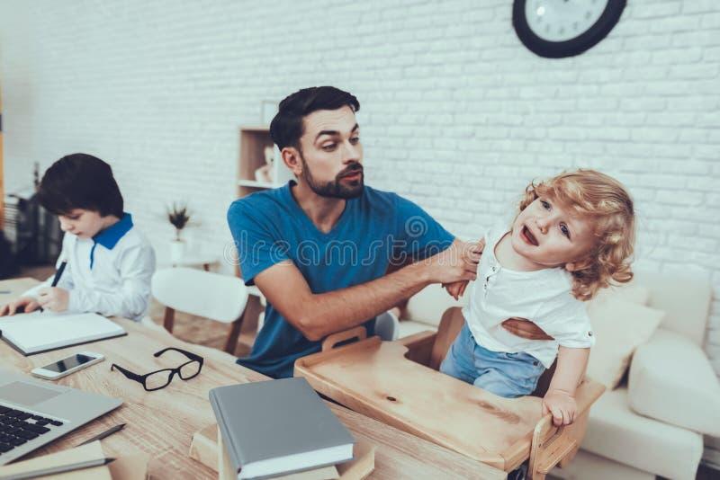 Il padre sta facendo un compito con il figlio immagini stock libere da diritti