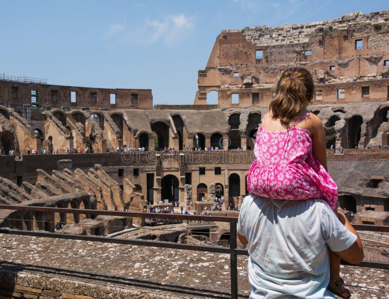 Il padre sta tenendo sua figlia sulle sue spalle per vedere l'arena interna del Colosseo fotografia stock libera da diritti