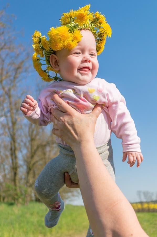 Il padre tiene il suo bambino Il bambino felice ha corona del dente di leone sulla sua testa immagine stock libera da diritti
