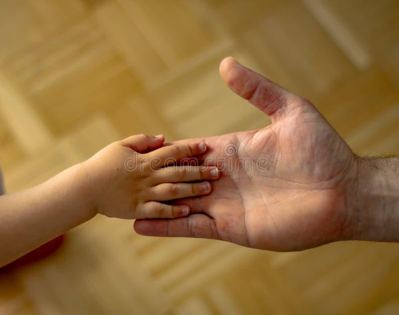 Il padre tiene la mano della sua piccola figlia fotografie stock libere da diritti