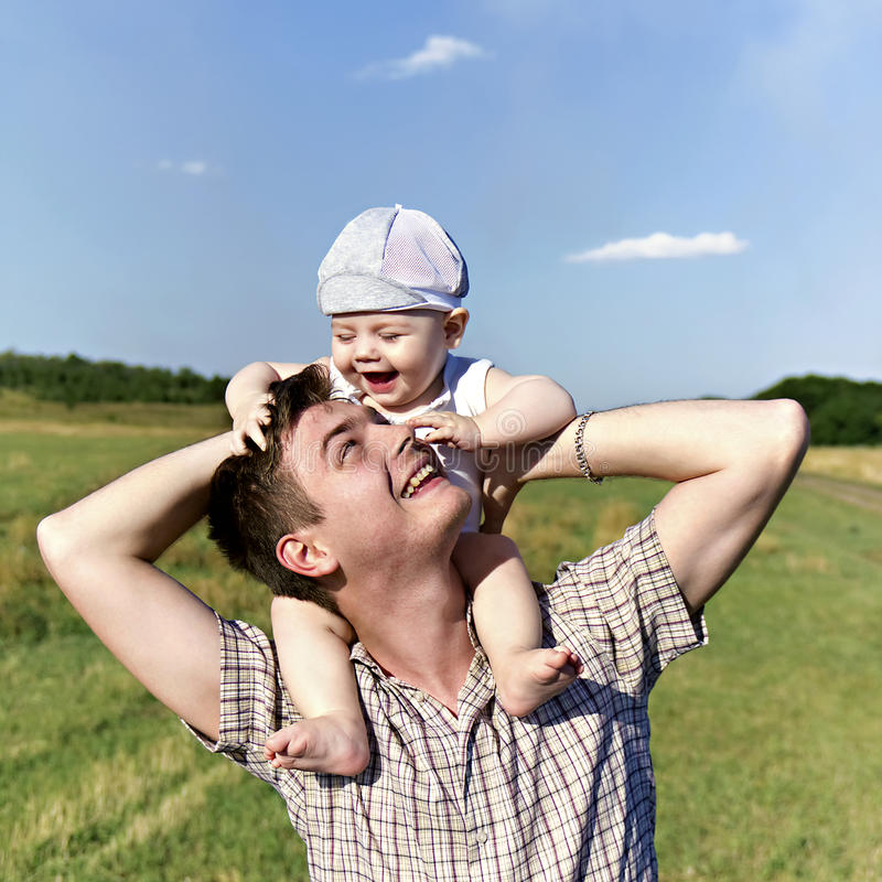 Il padre tiene un piccolo bambino sulle sue spalle immagini stock