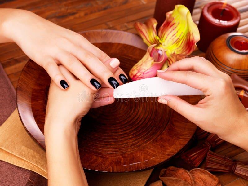 Il padrone del manicure fa il manicure sulle mani della donna immagine stock