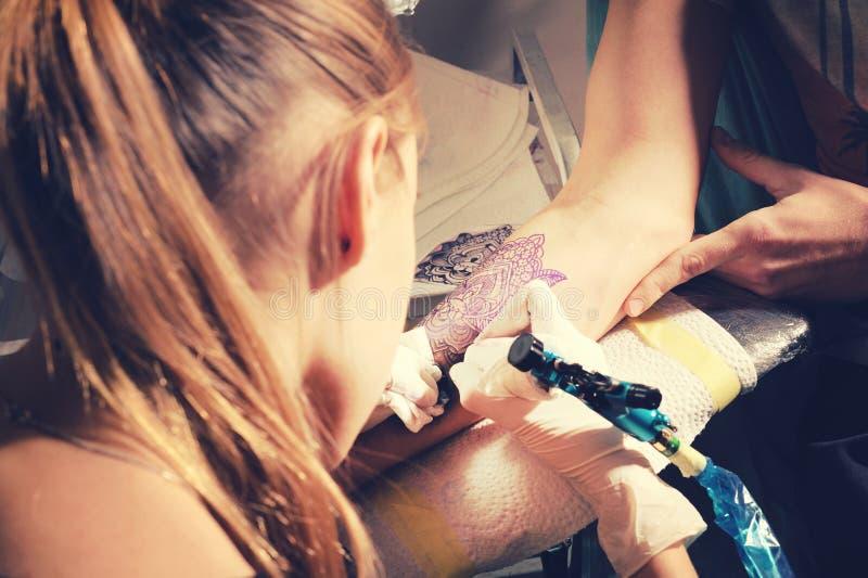 Il padrone del tatuaggio della donna fa il tatuaggio su una mano contro la somiglianza del blu violaceo di un tatuaggio futuro immagini stock