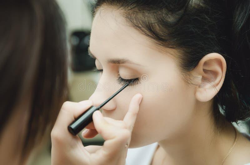 Il padrone di trucco dipinge gli occhi della ragazza Fa il trucco, primo piano immagine stock
