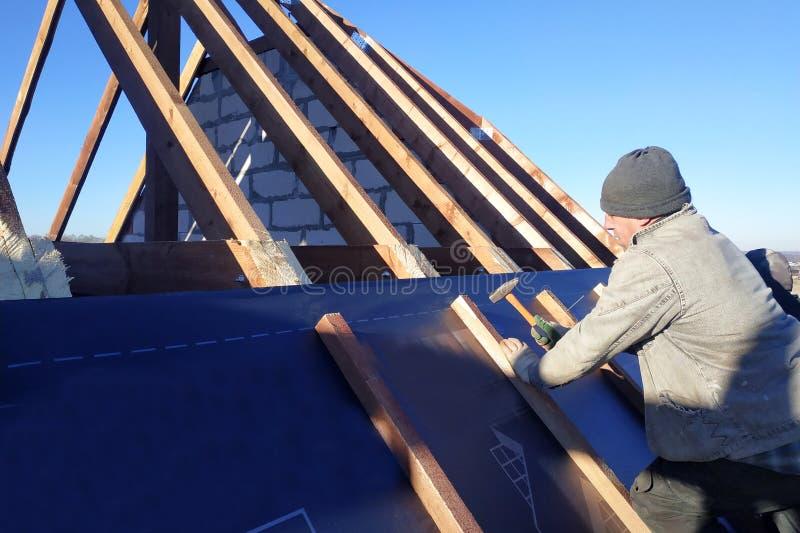 Il padrone inchioda le barre, riparanti questo gidrorizer alla trave, il cielo blu compare sui precedenti immagini stock libere da diritti