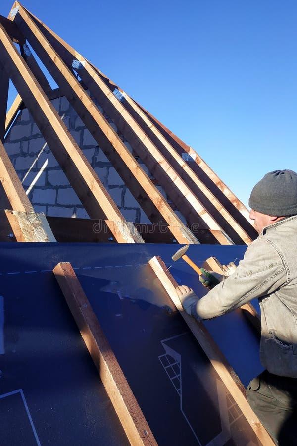 Il padrone inchioda le barre, riparanti questo gidrorizer alla trave, il cielo blu compare sui precedenti immagini stock