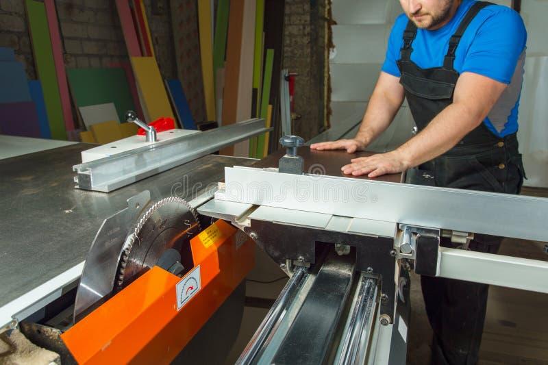 Il padrone prepara il pezzo in lavorazione per il taglio su una macchina circolare fotografia stock libera da diritti