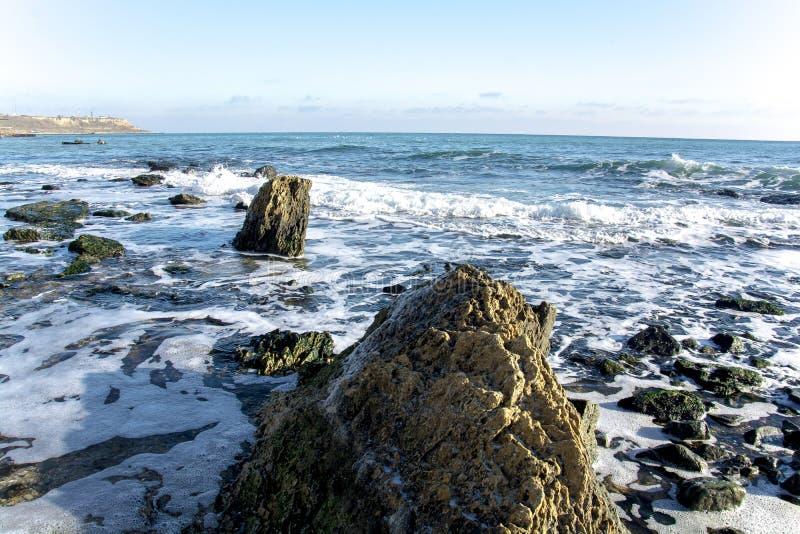 Il paesaggio del ‹del †del ‹del †del mare con il mare ondeggia cadere sulle rocce sparse lungo la spiaggia fotografia stock libera da diritti
