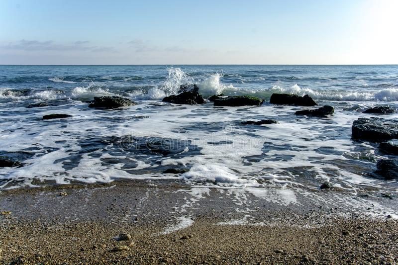 Il paesaggio del ‹del †del ‹del †del mare con il mare ondeggia cadere sulle rocce sparse lungo la spiaggia immagini stock