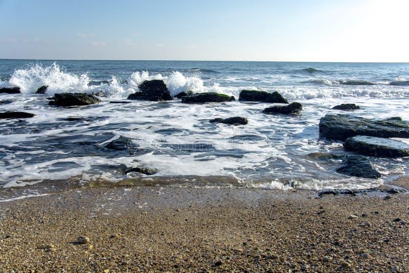 Il paesaggio del ‹del †del ‹del †del mare con il mare ondeggia cadere sulle rocce sparse lungo la spiaggia immagini stock libere da diritti