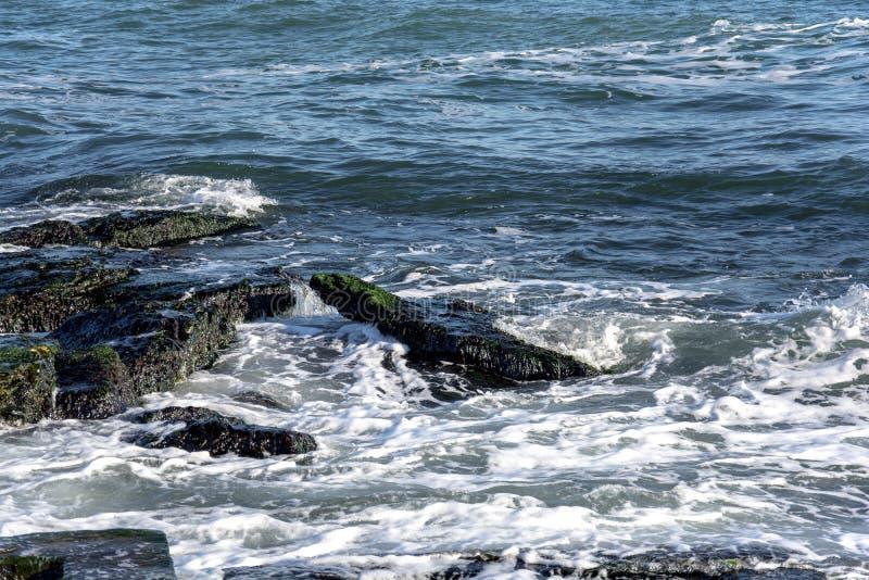 Il paesaggio del ‹del †del ‹del †del mare con il mare ondeggia cadere sulle rocce sparse lungo la spiaggia immagine stock