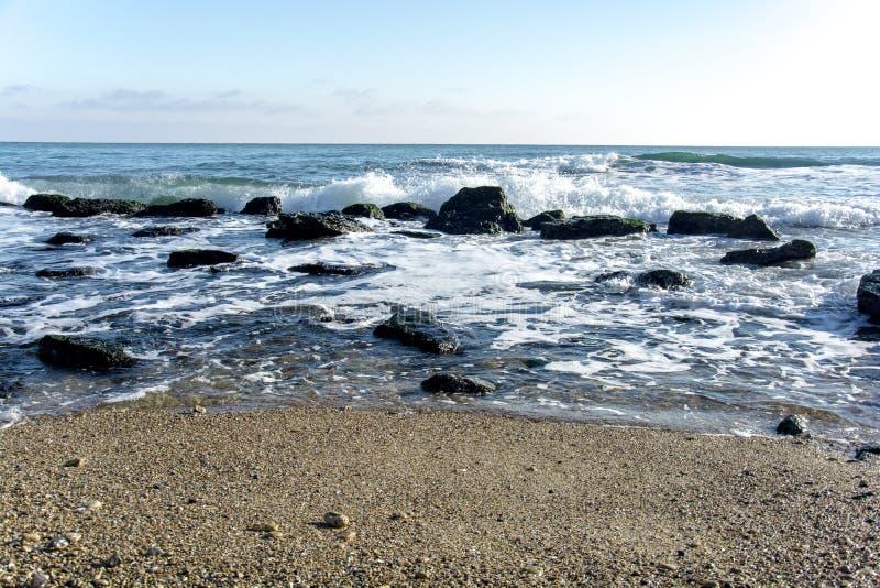 Il paesaggio del ‹del †del ‹del †del mare con il mare ondeggia cadere sulle rocce sparse lungo la spiaggia fotografia stock