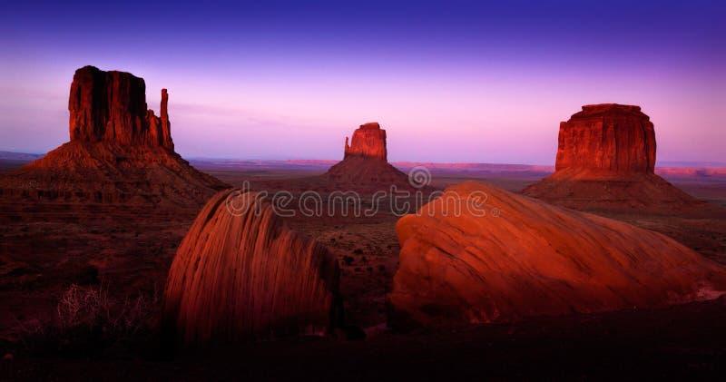 Il paesaggio della valle del monumento con i cieli porpora andRed le formazioni rocciose fotografia stock