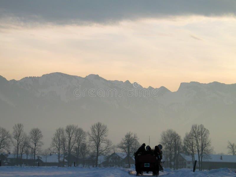 Il paesaggio di inverno, backlight, con il carrello trainato da cavalli fotografia stock