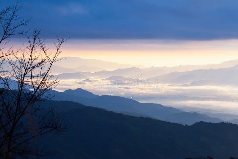 Il paesaggio sereno di catena montuosa blu di mattina si appanna, un villaggio e un fiume nella valle nebbiosa immagine stock