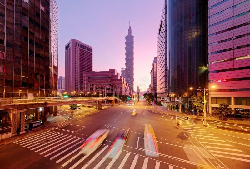 Il paesaggio urbano di un angolo di strada nella città del centro di Taipei con traffico trascina nella penombra di mattina fotografia stock libera da diritti