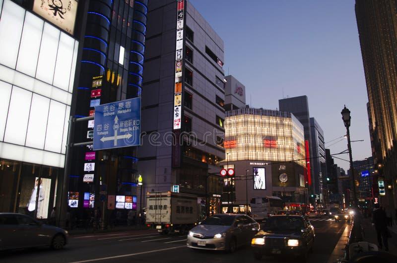 Il paesaggio urbano ed il popolo giapponese conducono l'automobile sulla strada di traffico nel crepuscolo fotografia stock