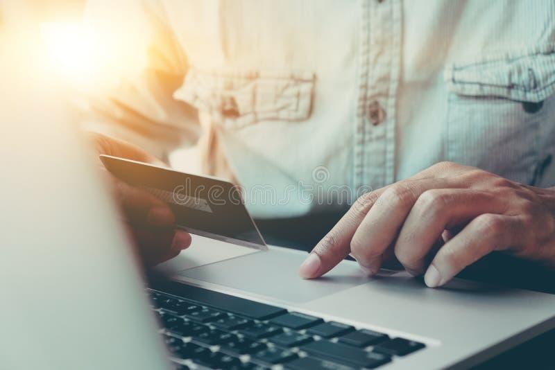 Il pagamento online, il ` s dell'uomo passa la carta del caredit della tenuta e computer portatile usando immagini stock libere da diritti