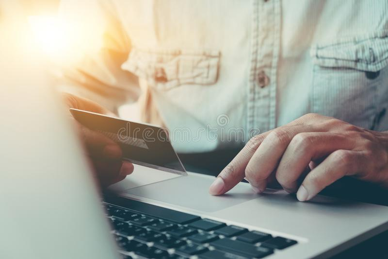 Il pagamento online, il ` s dell'uomo passa la carta del caredit della tenuta e computer portatile usando fotografia stock
