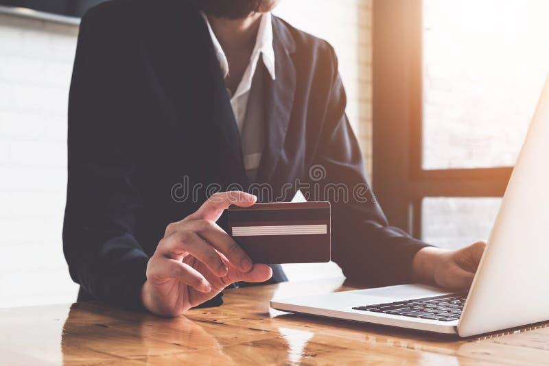 Il pagamento online, il ` s della donna di affari passa la tenuta della carta di credito e fotografia stock libera da diritti
