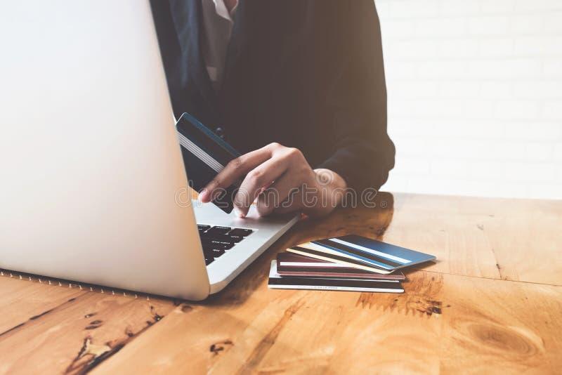 Il pagamento online, il ` s della donna di affari passa la tenuta della carta di credito e immagini stock libere da diritti