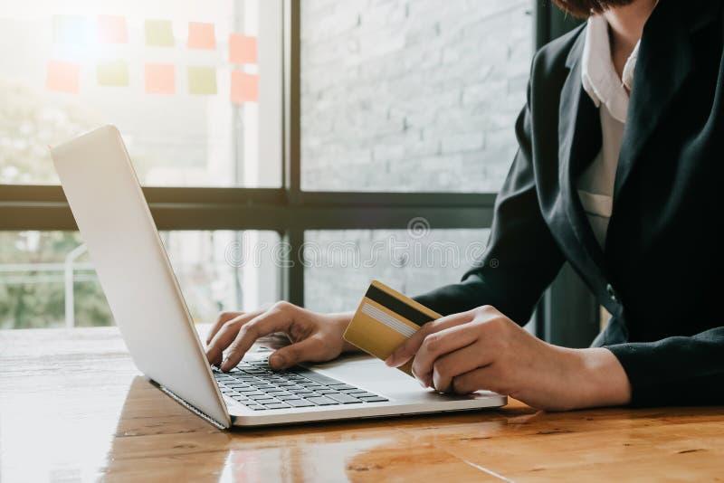 Il pagamento online, il ` s della donna di affari passa la tenuta della carta di credito e fotografie stock libere da diritti