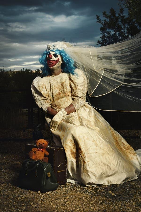 Il pagliaccio diabolico spaventoso in una sposa si veste al crepuscolo immagini stock libere da diritti