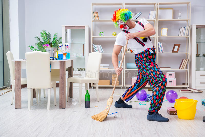 Il pagliaccio divertente che fa pulizia a casa immagini stock