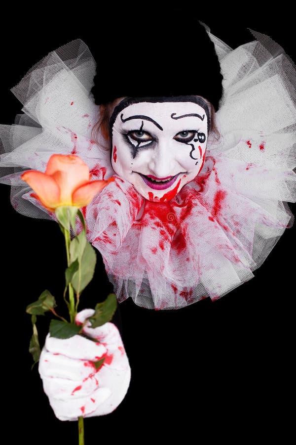 Il pagliaccio terrificante dà a spettatori una rosa fotografie stock libere da diritti