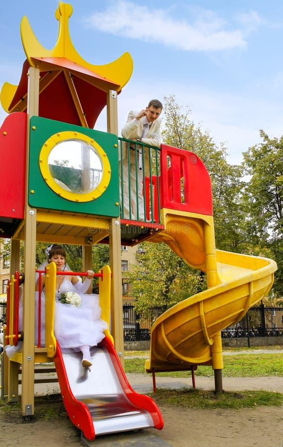 Il paio delle coppie neo-sposate scherza sul campo da gioco per bambini immagine stock libera da diritti