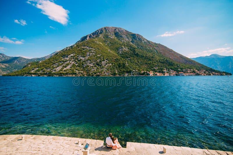 Il paio si siede sulla riva della baia di Cattaro, sull'isola di Gospa il od Skrpel fotografia stock