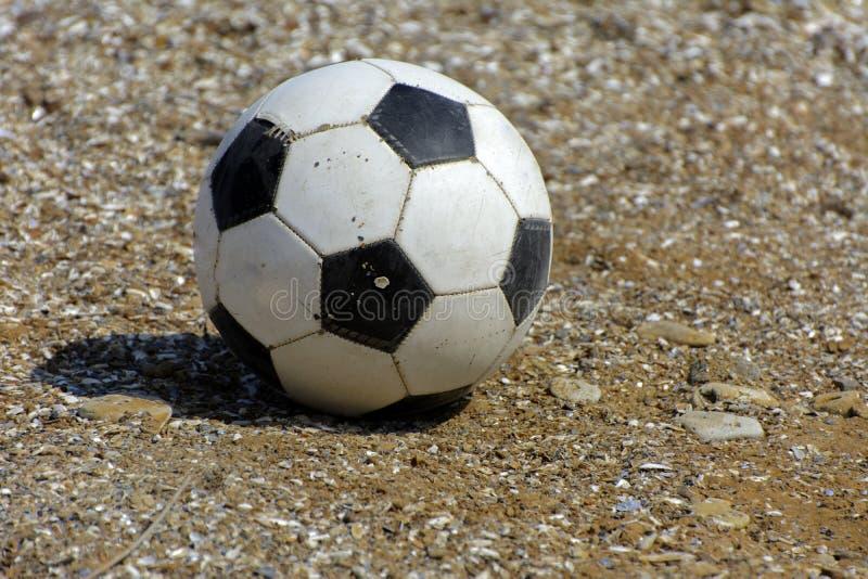 Il pallone da calcio di cuoio si trova sui precedenti della spiaggia sabbiosa S fotografia stock libera da diritti