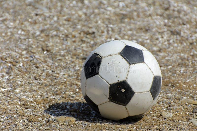 Il pallone da calcio di cuoio si trova sui precedenti della spiaggia sabbiosa S immagini stock