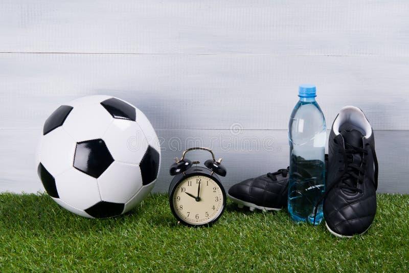 Il pallone da calcio, una bottiglia dell'acqua, gli stivali neri e una sveglia stanno sull'erba, su un fondo grigio immagine stock