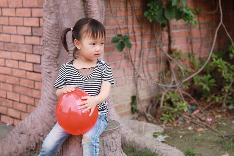 Il pallone rosso del piccolo della ragazza del bambino di sorriso gioco cinese adorabile sveglio felice di risata si diverte all' immagini stock