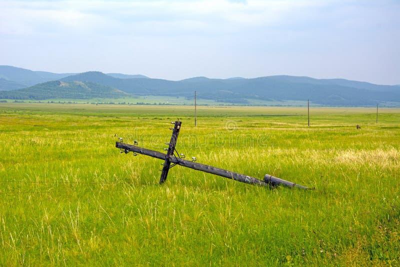 Il palo di legno della linea elettrica ha interrotto ed appeso sui cavi, contro il contesto del paesaggio della montagna immagini stock