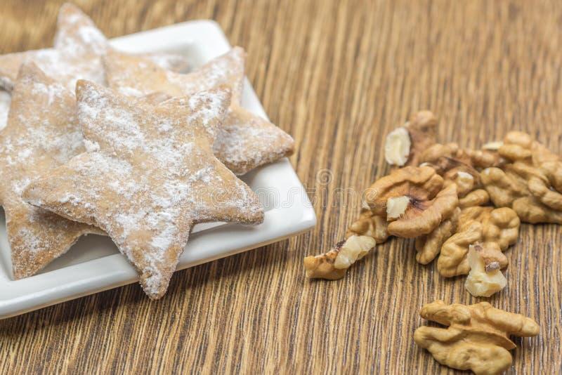Il pan di zenzero agglutina nella forma di stelle sul piatto ceramico bianco fotografie stock