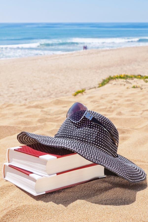Il Panama per il sole ed i libri di lettura sulla spiaggia. immagine stock