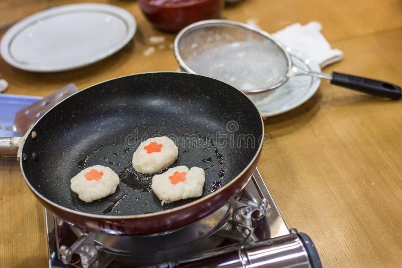 Il pancake di patata coreano è fritto facendo uso di una pentola nera immagine stock