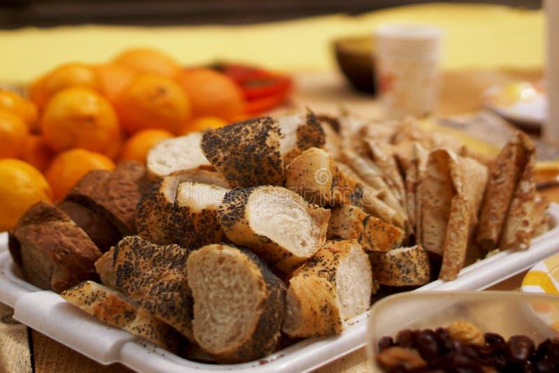Il pane con i semi e la crusca di papavero ha affettato a tè ed ai pancake con lavash immagine stock