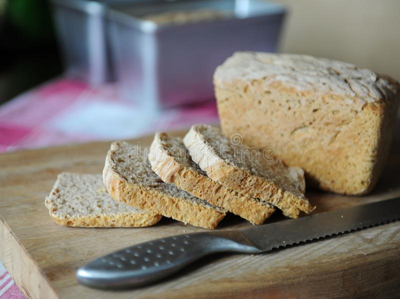 Il pane fresco su un fermento della segale senza lievito ha tagliato su un tagliere di legno su una tovaglia a quadretti fotografia stock libera da diritti