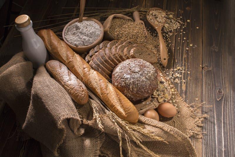 Il pane integrale, il latte, la farina ed il panno insaccano sulla tavola di legno fotografia stock