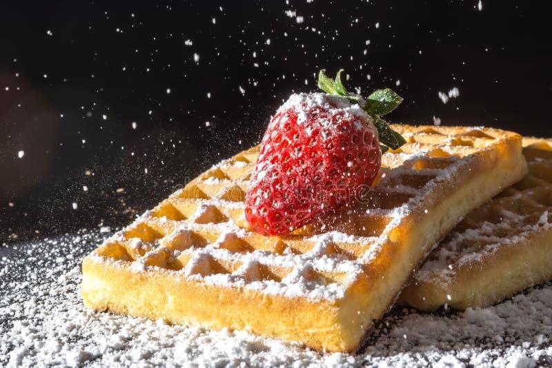 Il pane tostato dolce waffles con la fragola con le foglie sulla cima e sul vagliare la polvere di versamento dello zucchero nel  fotografia stock libera da diritti